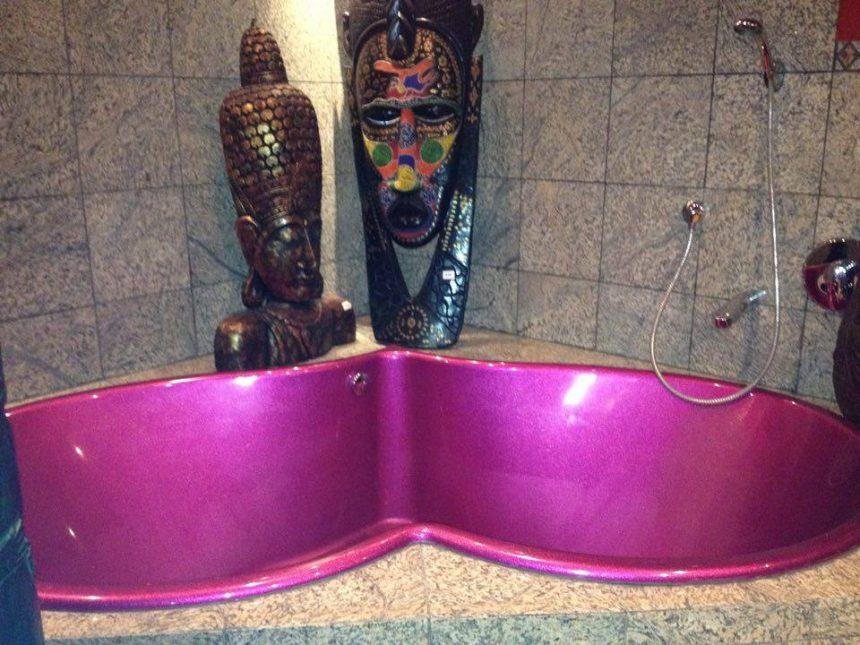 Badewanne in Herzform vor geschnitztem Maskengedöns für die Stimmung.